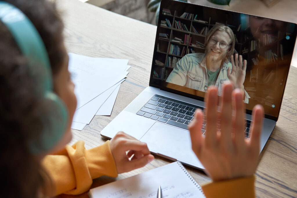 Hispanic teen girl school college student distance learning waving hand studying with online teacher on laptop screen. Elearning zoom video call, videoconference class with tutor. Over shoulder view.